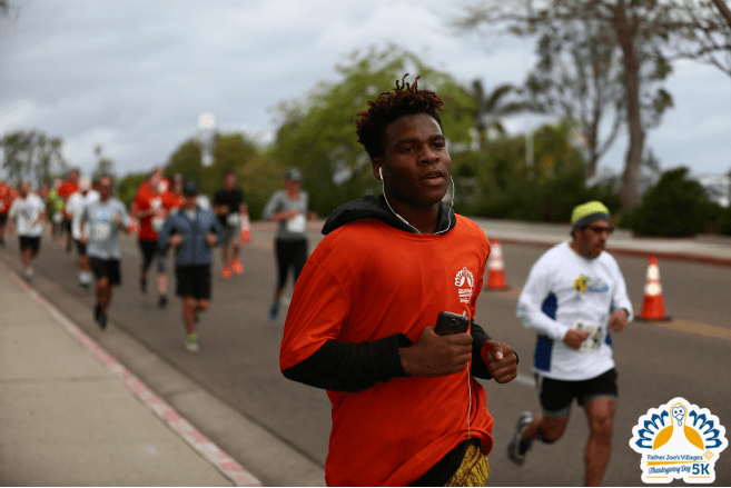 Thanksgiving 5K San Diego | Kid in orange Father Joe's Villages Thanksgiving Day 5K shirt running alongside others.