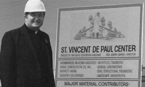 Father Joe next to a sign for St. Vincent De Paul Center