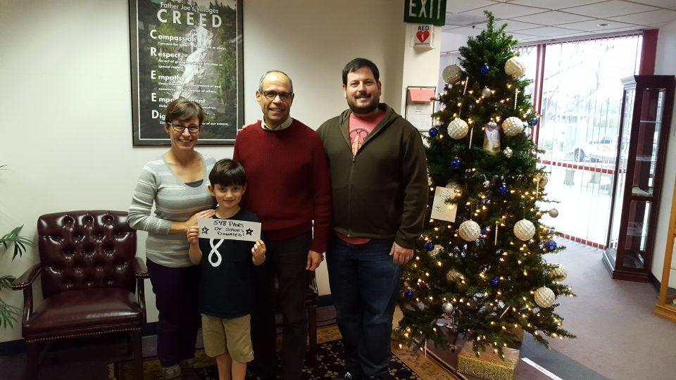 deacon Jim with a family in front of Christmas tree