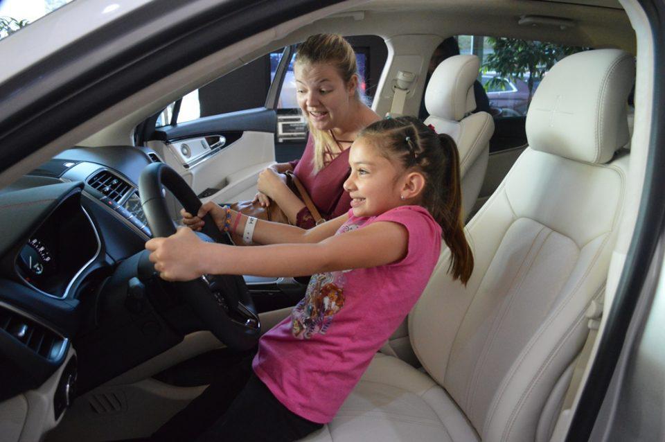 a little girl pretending to drive a car