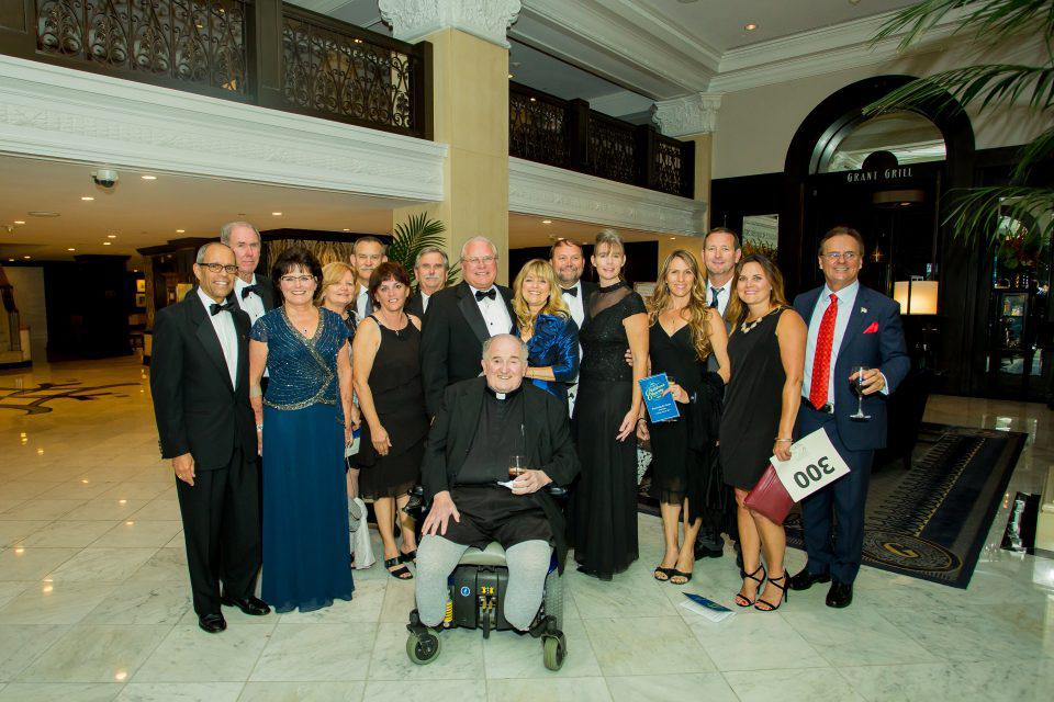 Guests of the Children's Charity Gala gather for a picture in the grand U.S. Grant Hotel.
