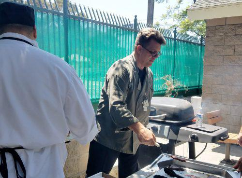 Culinary Arts Program instructor helps students serve up the perfect burger.