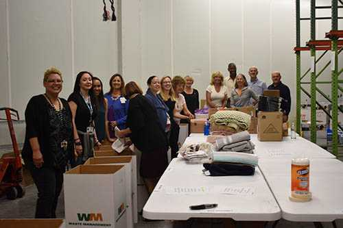 Father Joe and Rotary Club members filling the welcome home kits | San Diego Downtown Breakfast Rotary Club