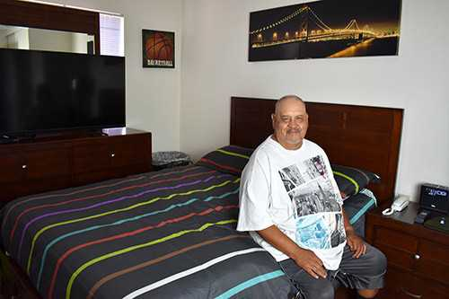 Senior Living Homeless in San Diego | Sebastian sits on the edge of his bed in his new apartment.