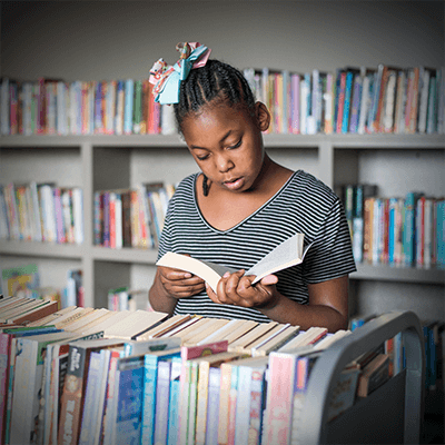Tutoring Programs | A little girl reads in the Therapeutic Childcare library.