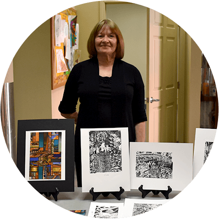 Elaine's Story: Healing Through Art | Elaine stands next to her colorful collage art and black and white etchings.