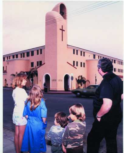 Father Joe and children in front of the Family Health Services Building