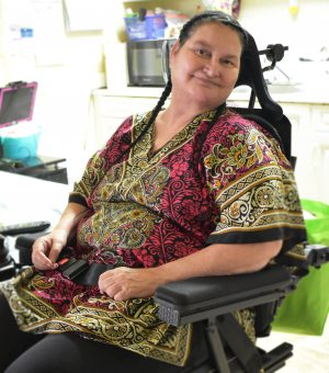 Rebecca sitting in her wheelchair in her Permanent Housing apartment.