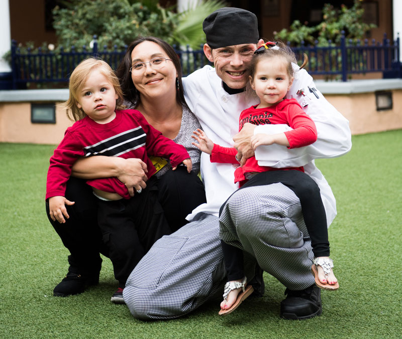 Nina, Stephen and their two kids pose together on the JKC lawn | homeless family help