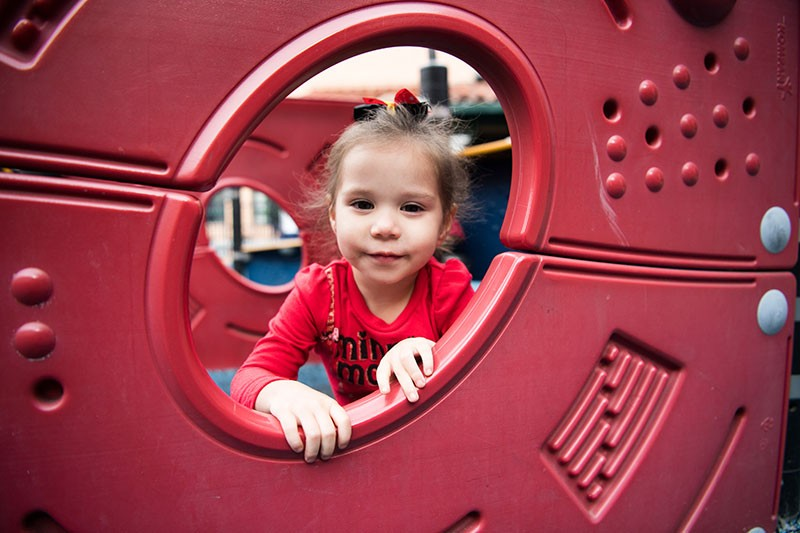 Child peeks through a playground structure. | homeless family help