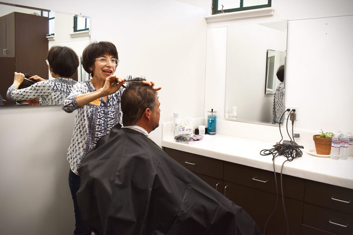 Volunteer hairdresser cuts a client's hair before his interview. | haircuts for homeless