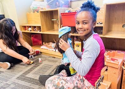 Little girl plays with doll in Father Joe's Villages Therapeutic Childcare Center. | 2018 Annual Report