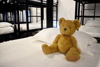 A teddy bear sits on a bed at the Bridge Shelter.